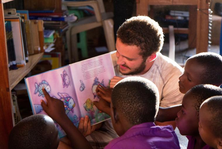 Teacher reading book to young children
